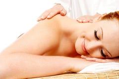 Nätt kvinna som får massage i en brunnsortmitt Royaltyfri Bild