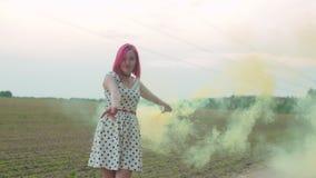 Nätt kvinna som går i färgrök över fält