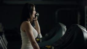 Nätt kvinna som går på trampkvarnen som talar på telefonen arkivfilmer