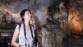 Nätt kvinna som går till och med en grotta stock video