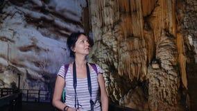 Nätt kvinna som går till och med en grotta arkivfilmer