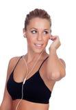 Nätt kvinna som gör lyssnande musik för kondition med hörlurar royaltyfri fotografi