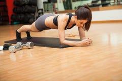 Nätt kvinna som gör plankor på en idrottshall Arkivfoto