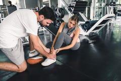 Nätt kvinna som har skada under övning i idrottshall medan hennes par som tar första hjälpen-, olycks- och sportkonditionbegrepp royaltyfri foto