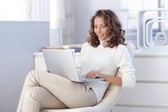 Nätt kvinna som hemma använder bärbar datordatoren Arkivbild