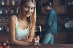 Nätt kvinna som hemma dricker något vin i kök arkivfoton