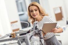 Nätt kvinna som kontrollerar skrivaren 3D via minnestavlan Arkivbild