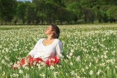Nätt kvinna som kopplar av i fält för vita blommor arkivfoton