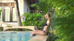 Nätt kvinna som kopplar av på poolside, når att ha simmat på sommarferie i semesterorthotell Ung kvinna som poserar den utomhus-  arkivfilmer