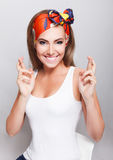 Nätt kvinna som korsar henne fingrar för bra lycka fotografering för bildbyråer