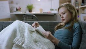 Nätt kvinna som läser en bok på en soffa stock video