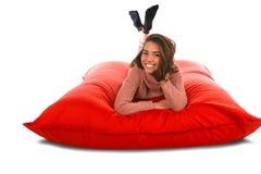 Nätt kvinna som ligger på den formade sittkuddesoffan för röd fyrkant som isoleras på Royaltyfria Bilder
