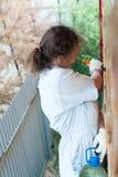 Nätt kvinna som målar henne hus Fotografering för Bildbyråer