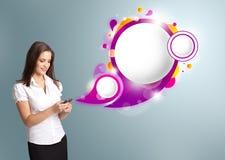 Nätt kvinna som rymmer en telefon och framlägger abstrakt anförandebubb Royaltyfri Foto