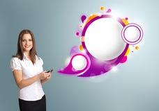 Nätt kvinna som rymmer en telefon och framlägger abstrakt anförandebubb Arkivfoton