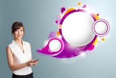 Nätt kvinna som rymmer en telefon och framlägger abstrakt anförandebubb Arkivfoto