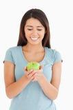 Nätt kvinna som rymmer ett grönt äpple fotografering för bildbyråer