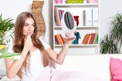 Nätt kvinna som sätter på makeup Arkivbild