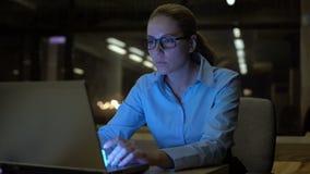 Nätt kvinna som sent arbetar på natt för bärbar dator - i regeringsställning, samvetsgrann anställd stock video