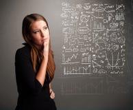 Nätt kvinna som ser aktiemarknadgrafer och symboler Arkivbild