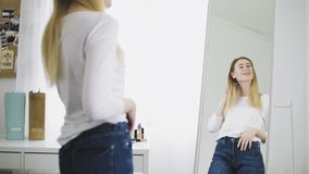 Nätt kvinna som ser i spegeln som undersöker hennes reflexion stock video