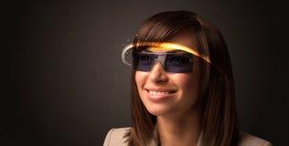 Nätt kvinna som ser med futuristiska tekniskt avancerade exponeringsglas Arkivfoton