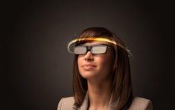 Nätt kvinna som ser med futuristiska tekniskt avancerade exponeringsglas Arkivfoto