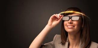 Nätt kvinna som ser med futuristiska tekniskt avancerade exponeringsglas Royaltyfria Bilder