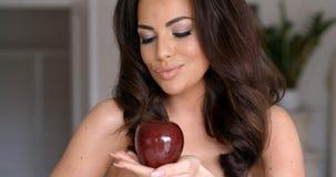 Nätt kvinna som ser röda Apple på hennes hand Arkivfoton
