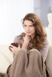 Nätt kvinna som sitter på dricka tea för sofa Royaltyfria Foton