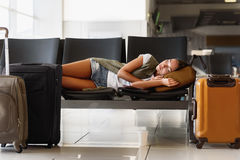 Nätt kvinna som sover i flygplats arkivbild