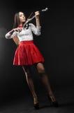 Nätt kvinna som spelar fiolen på en svart bakgrund Arkivfoto