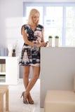 Nätt kvinna som texting på mobilt hemmastatt Fotografering för Bildbyråer