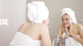 Nätt kvinna som tvättar hennes framsida med vatten arkivfilmer