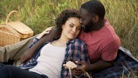 Nätt kvinna som tycker om lukten av den älskade mannen som tillsammans ligger på hans bröstkorg, tidsfördriv royaltyfri foto
