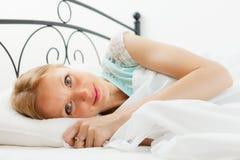 Nätt kvinna som vaknar i hennes säng Arkivfoto