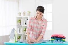 Nätt kvinnaarbetare som stryker alla rynkiga kläder Arkivbilder