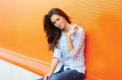 Nätt kvinnabrunett utomhus mot den färgrika väggen i sommar Royaltyfri Fotografi