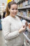Nätt kvinnaköpandeledbulb i supermarket som rymmer den ledde kulan i hand Iklädd vit stucken tröja arkivbild