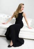 Nätt kvinnasammanträde på soffan för vitt läder royaltyfria foton