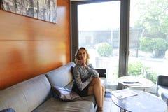 Nätt kvinnasammanträde på soffan nära fönster hemma royaltyfria foton