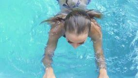 Nätt kvinnasimning i semesterortpöl på den soliga dagen Härlig kvinna som tycker om sötvatten i simbassäng på sommar arkivfilmer