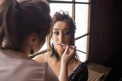 Nätt kvinnasminkkonstnär som applicerar makeup till den härliga latina flickan Arkivfoton