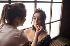 Nätt kvinnasminkkonstnär som applicerar makeup till den härliga latina flickan Royaltyfri Fotografi