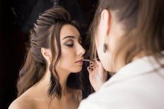 Nätt kvinnasminkkonstnär som applicerar makeup till den härliga latina flickan Royaltyfri Foto