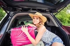 Nätt kvinnastående på bilstammen med resväskor Royaltyfri Bild