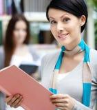 Nätt kvinnastudent på arkivet mot bokhyllor Arkivbilder