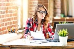 Nätt kvinnlig arkitekt Sitting And Working med bärbara datorn arkivbild