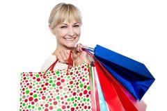 Nätt kvinnlig bärande shopping hänger lös över knuffar Arkivfoto