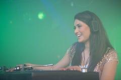 Nätt kvinnlig discjockey som spelar musik royaltyfri fotografi